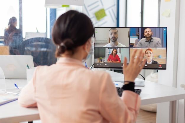 Empresária falando remotamente com freelancers no local de trabalho do escritório corporativo usando máscara facial como prevenção de segurança, mantendo o distanciamento social usando máscara facial.