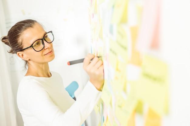 Empresária faz uma anotação em uma etiqueta de papel