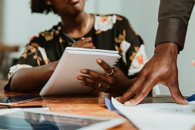 Empresária fazendo anotações em uma reunião