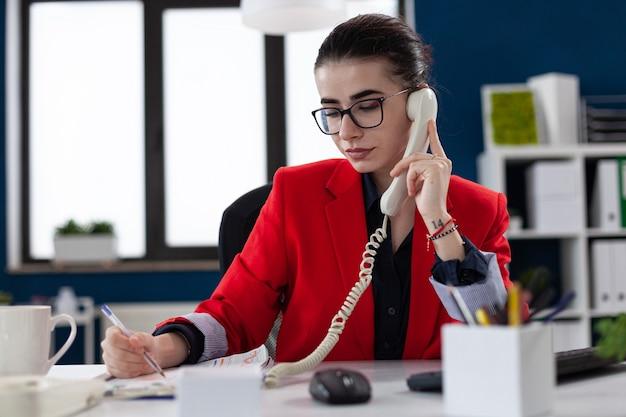 Empresária fazendo anotações na área de transferência, sentada na mesa do escritório corporativo, enquanto toma