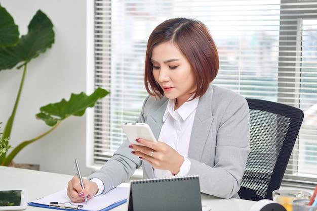 Empresária fazendo anotações olhando para um celular no escritório. empreendedor de mulher sentado à mesa escrevendo notas enquanto trabalha no celular.