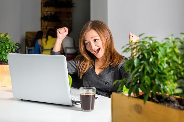 Empresária feliz animada com os braços erguidos, sentado à mesa com o laptop, comemorando seu sucesso