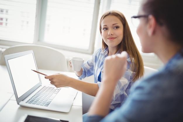 Empresária feliz apontando no laptop com o colega no escritório