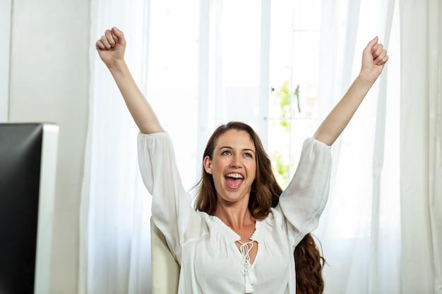 Empresária feliz com os braços levantados no escritório