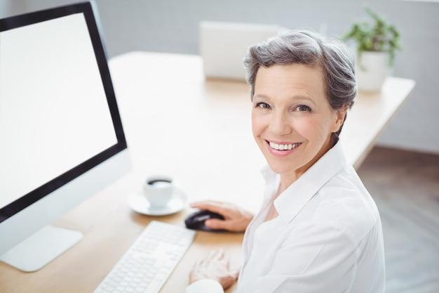 Empresária feliz sentado na mesa do computador