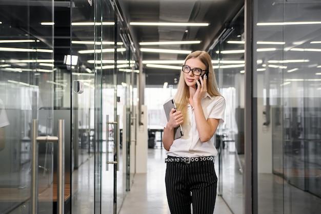 Empresária feliz tendo conversa de telefone legal. mulher sorridente na blusa branca do escritório falando no celular e aprendendo boas notícias. conceito de boas notícias