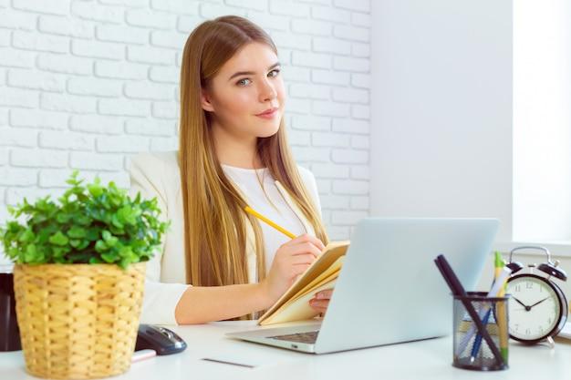 Empresária feliz trabalhando no laptop no escritório