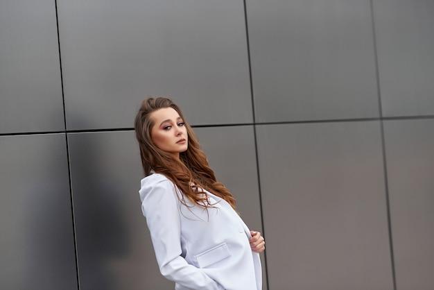 Empresária fica na frente de uma parede em um terno branco