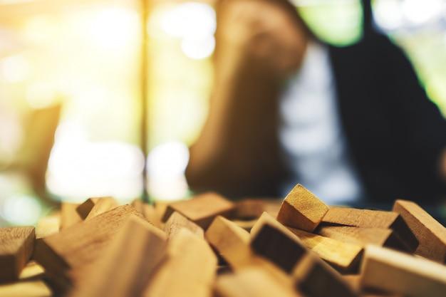 Empresária ficar estressada ao ter um problema no trabalho no escritório com blocos de madeira do jogo da torre de queda na mesa