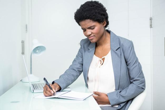 Empresária grávida escrevendo no notebook no escritório
