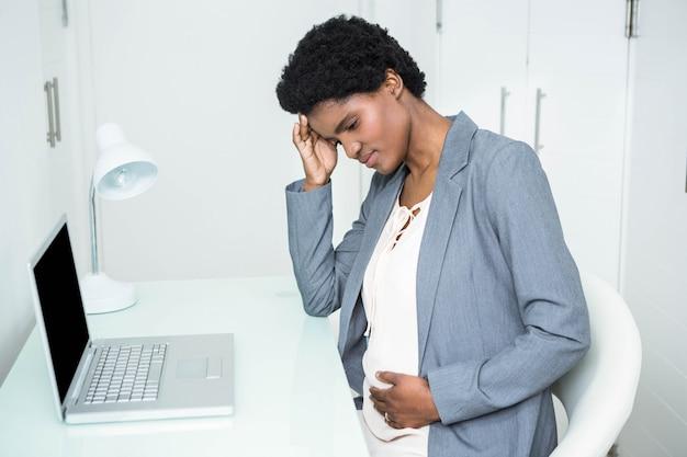 Empresária grávida tocando sua cabeça e barriga no escritório