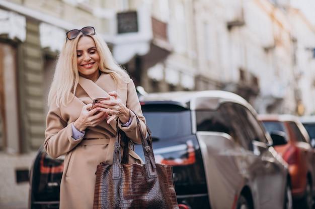 Empresária idosa falando no telefone por seu carro eletro