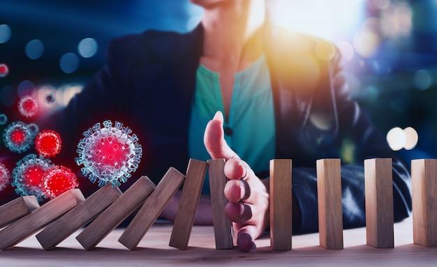 Empresária impede uma queda na cadeia de vírus como jogo de dominó. conceito de prevenção de crises e falhas nos negócios.