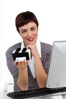 Empresária incandescente segurando um titular de cartão de visita