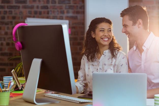 Empresária, interagindo com o colega de trabalho enquanto trabalha no computador