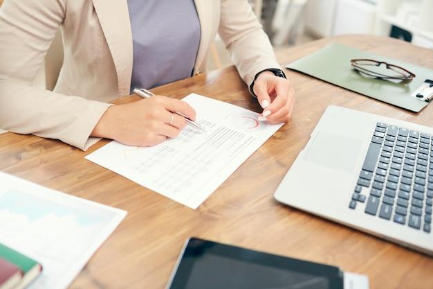 Empresária irreconhecível, lendo o relatório de estatísticas