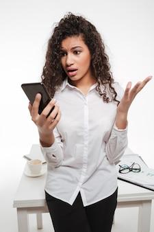Empresária jovem africana atônita espantada em pé e usando telefone celular