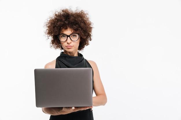 Empresária jovem atraente em óculos usando laptop