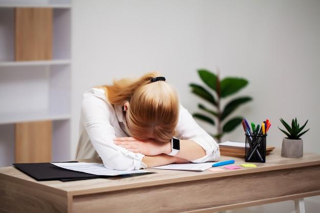 Empresária jovem cansada, exausta no local de trabalho em seu escritório