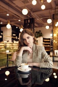 Empresária jovem confiante em roupas casuais inteligentes bebe café