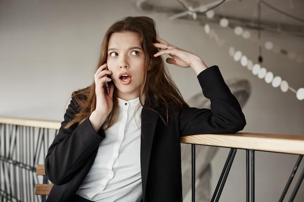 Empresária jovem preocupada no café falando por telefone