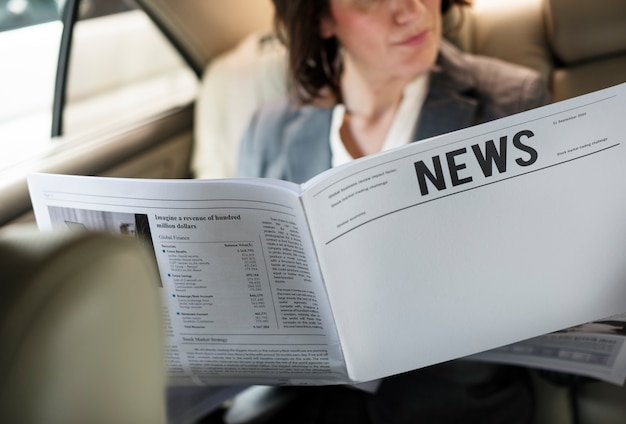 Empresária lendo jornal carro dentro