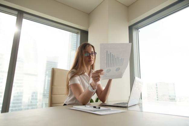 Empresária, lendo o documento com gráficos