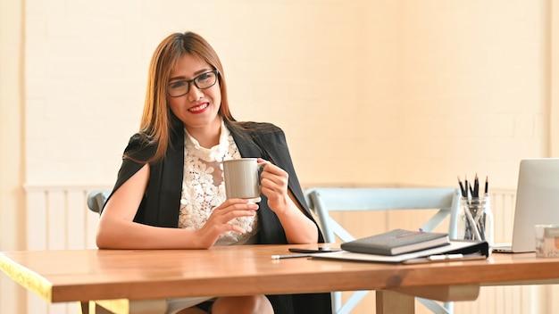 Empresária, localização e segurando uma xícara de café