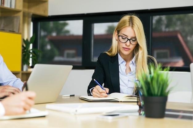 Empresária loira atraente, trabalhando no escritório moderno