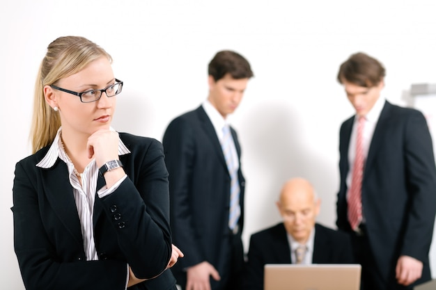 Empresária loira séria com pessoas borradas