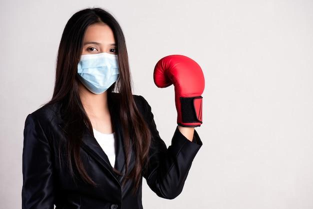 Empresária, luvas de boxe vermelhas e máscara facial, pronta para o coronavírus