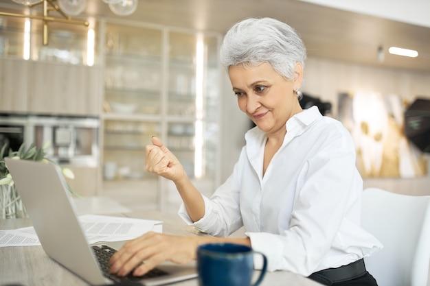 Empresária madura usando laptop para trabalho remoto, sentada na mesa tomando café