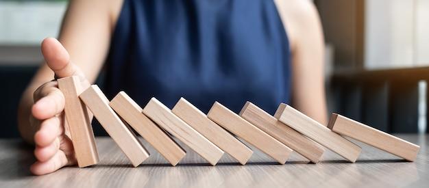Empresária mão parando dominós de madeira caindo