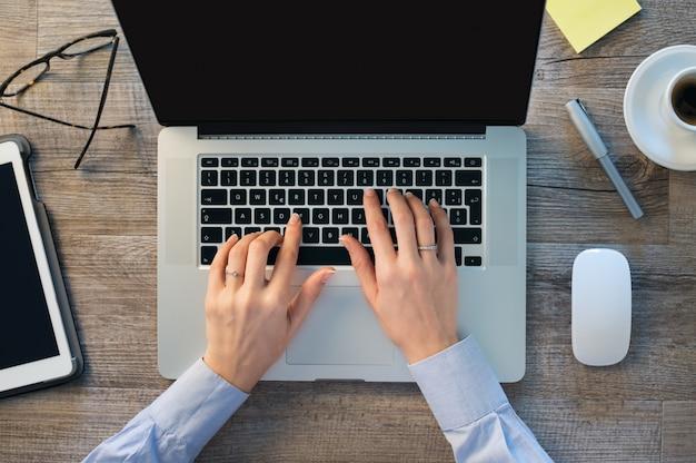 Empresária mãos digitando no laptop