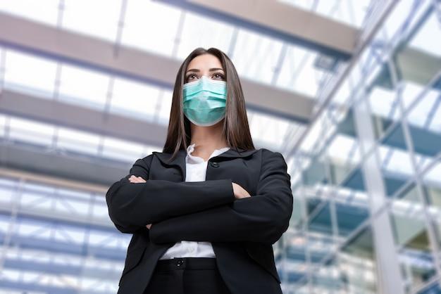 Empresária mascarada na frente de seu escritório, pandemia de coronavírus e conceito de trabalho