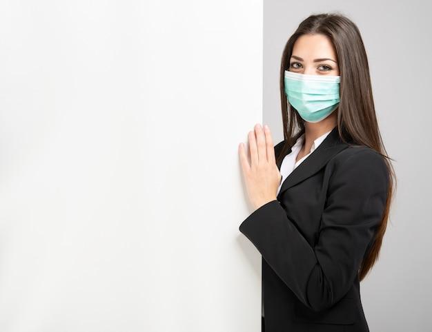 Empresária mascarada no fron de uma parede branca para colocar seu texto