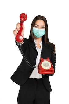 Empresária mascarada usando um telefone vintage durante uma pandemia de coronavírus