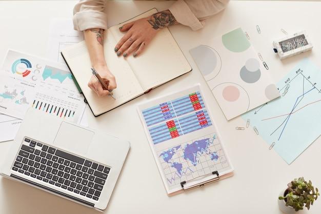 Empresária moderna escrevendo no planejador enquanto está sentado à mesa, copie o espaço