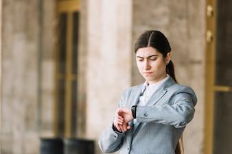 Empresária moderna olhando para o relógio ao ar livre