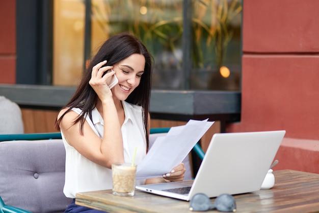 Empresária morena alegre tem conversa telefônica, satisfeita com consultoria, conversa com o operador de serviço, vestida com blusa elegante, mantém documentos em papel, funciona no computador portátil