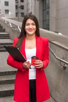 Empresária morena ao ar livre com casaco de leitura