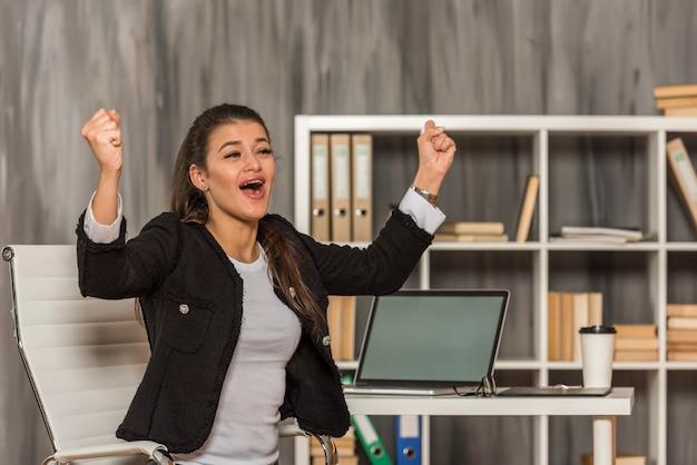 Empresária morena comemorando em seu escritório