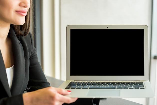 Empresária morena mostrando laptop