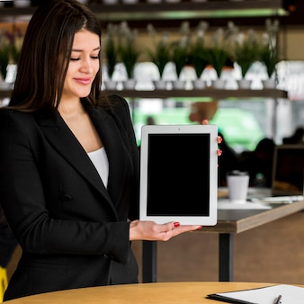 Empresária morena mostrando um tablet