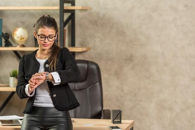 Empresária morena olhando para o relógio