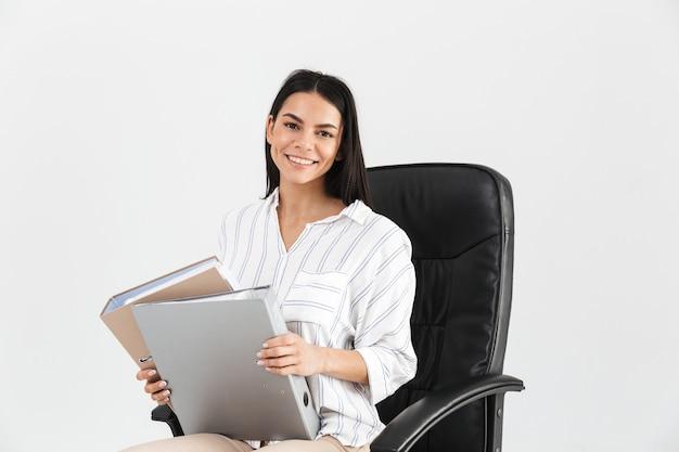 Empresária morena sorrindo e segurando um monte de pastas de papel enquanto está sentada na poltrona preta no escritório isolado sobre a parede branca
