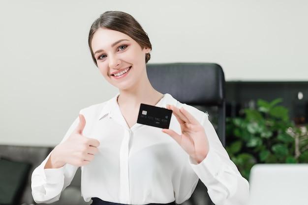 Empresária mostra cartão de crédito e polegares para cima no escritório