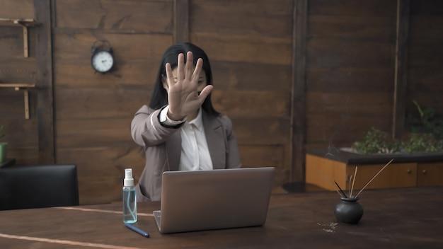 Empresária mostra sinal de stop com a palma da mão estendida para a frente. mulher asiática, trabalhando com um computador no escritório