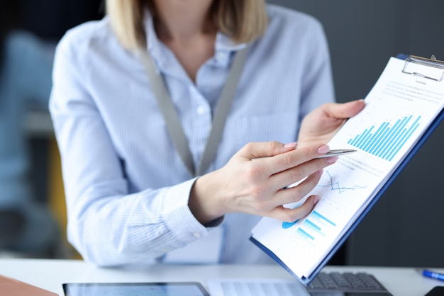 Empresária mostrando caneta esferográfica em documentos com gráficos close-up