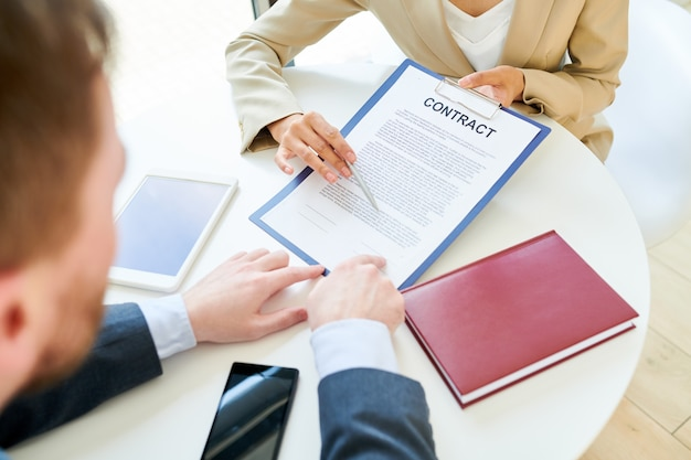 Empresária mostrando contrato para cliente fechar